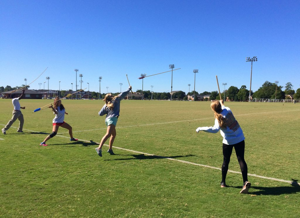 Students throwing the atlatls, a Native American spear-throwing device