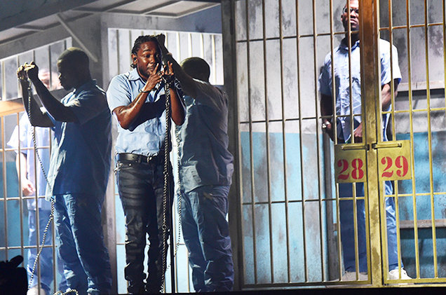 "Rapper Kendrick Lamar performing the song ""Alright"" in chains, with young black men in jail cells behind him"