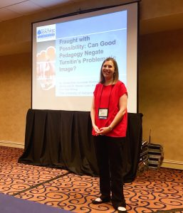 Natalie Loper standing in front of the presentation title slide