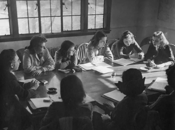 students gathered around a conference table smoking, 1950s