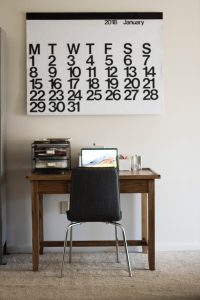 Chair and desk with calendar on the wall.