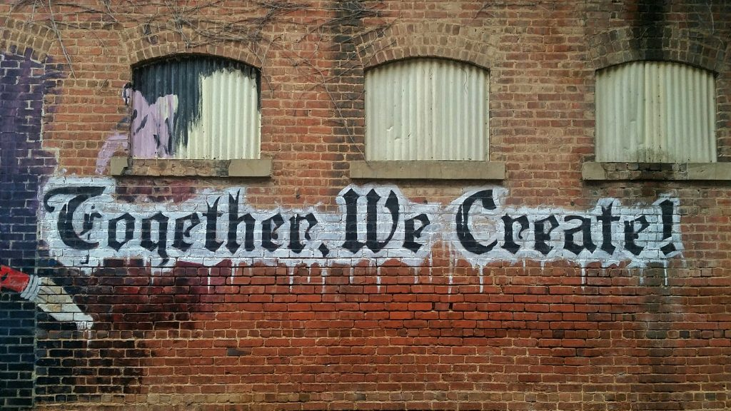 "graffiti on wall saying ""together we create"""