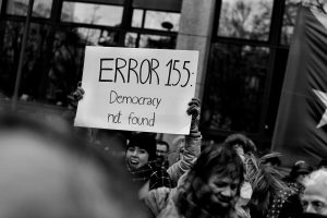 "Protestor with sign saying ""error 155: democracy not found"""