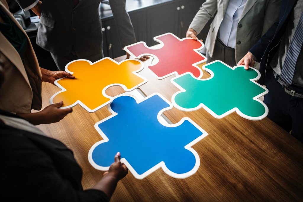 people holding large puzzle pieces on a table