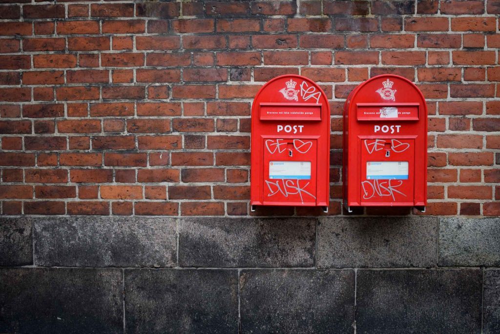 Two UK post boxes on a brick wall