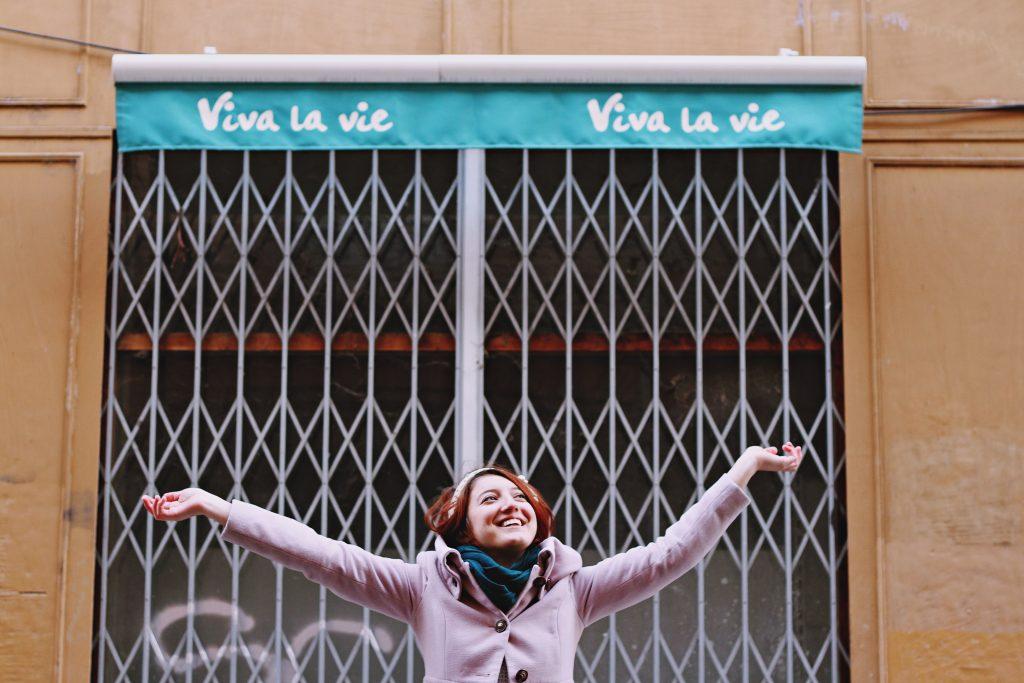 "Happy young woman under a banner saying ""Vive la vie"""