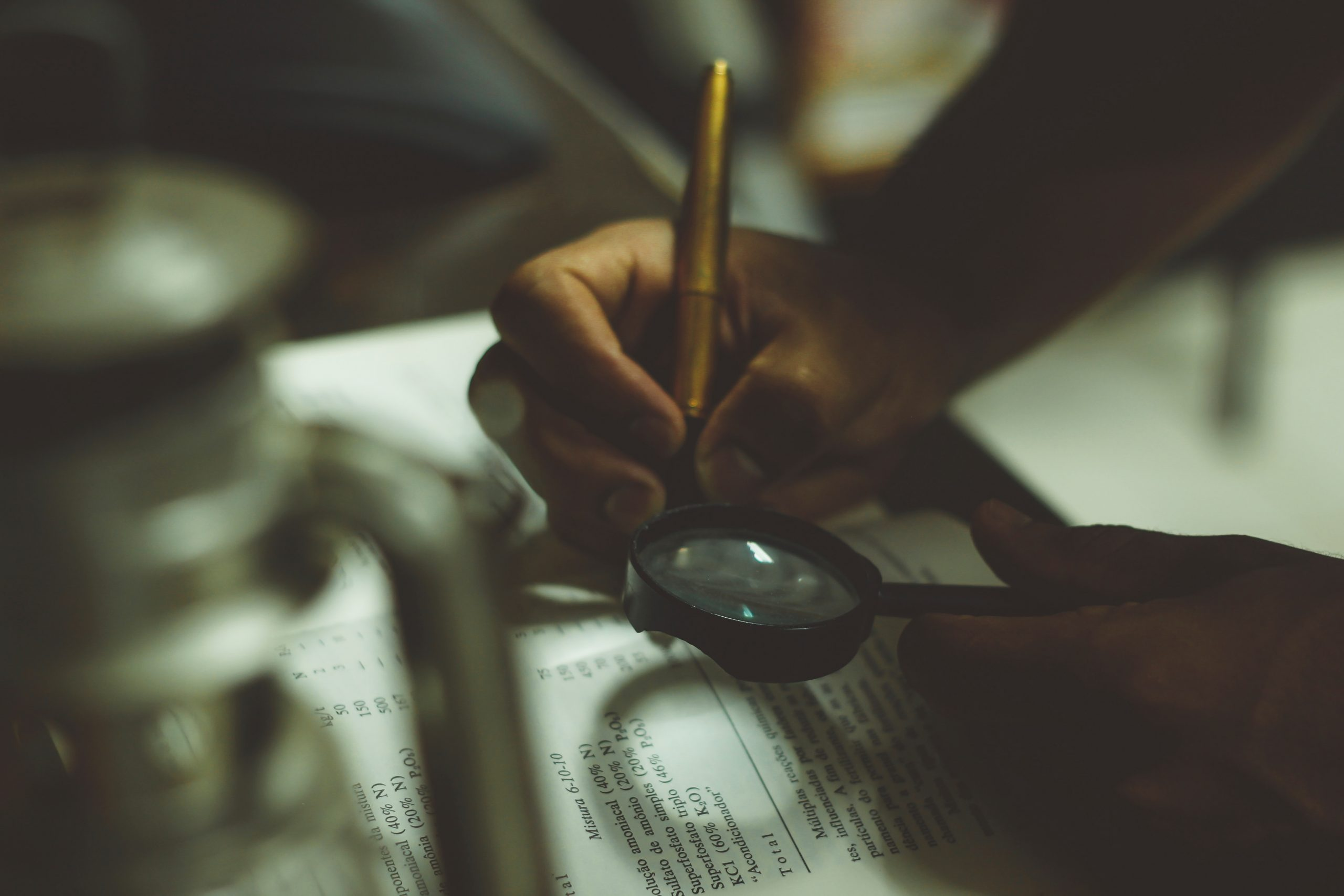 hands holding pen and magnifying glass over a book