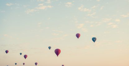 blue sky dotted with hot air balloons