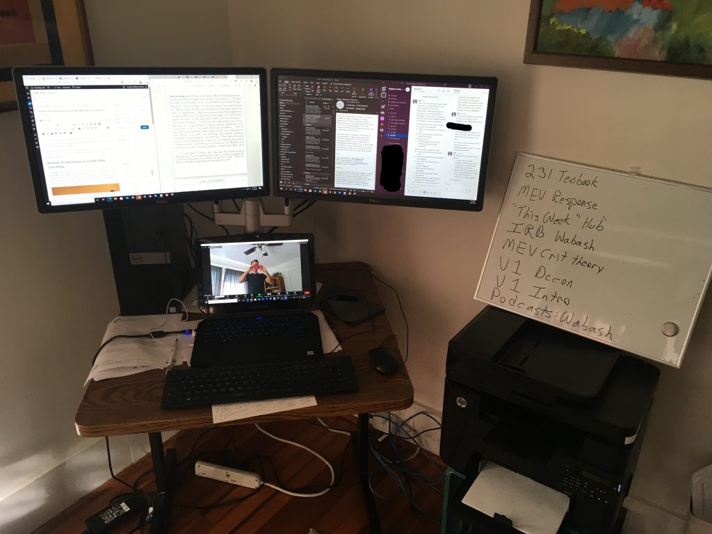 desk with dual display monitors and a laptop